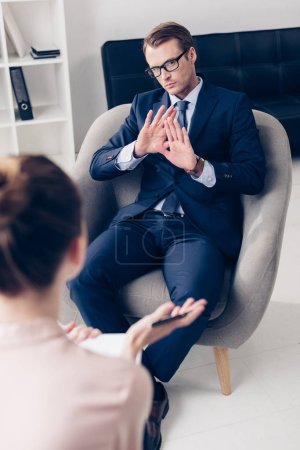 high angle view of handsome businessman showing no gesture while giving interview to journalist in office