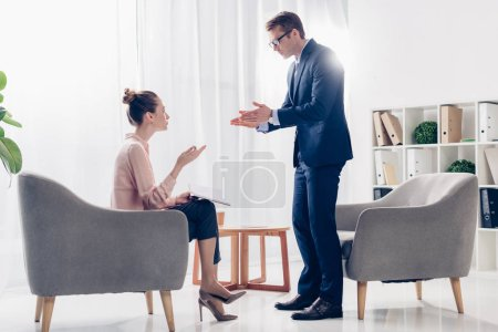 irritated businessman standing and gesturing while giving interview to journalist in office
