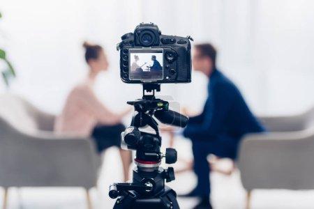 Photo pour Homme d'affaires donnant une interview à un journaliste au bureau, caméra sur trépied au premier plan - image libre de droit