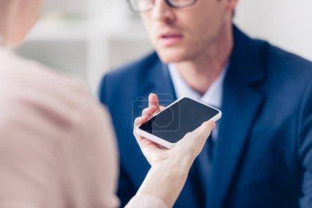 Photo pour Image recadrée de l'homme d'affaires donnant une interview à un journaliste avec smartphone avec écran blanc au bureau - image libre de droit