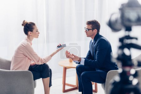 selective focus of handsome businessman giving interview to journalist in office