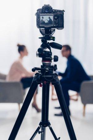 Photo pour Vue de côté de l'homme d'affaires donnant une interview au journaliste au bureau, caméra sur trépied au premier plan - image libre de droit