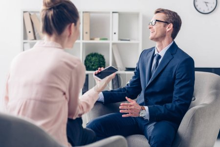 laughing handsome businessman giving interview to journalist in office