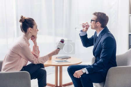 side view of handsome businessman drinking water while giving interview to journalist with microphone in office