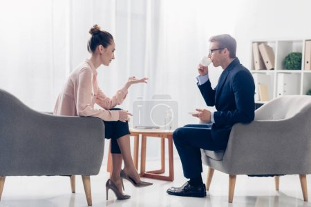 side view of attractive journalist asking questions while businessman drinking coffee in office