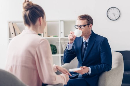 handsome businessman drinking coffee, journalist waiting for interview in office