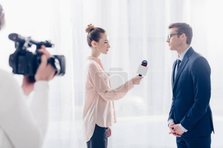 side view of handsome businessman in glasses giving video interview to journalist in office