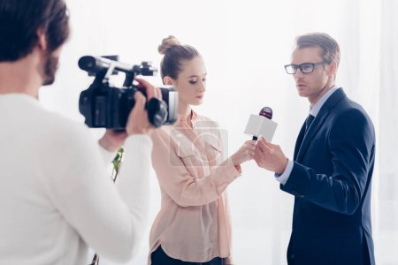 handsome businessman in glasses giving video interview to journalist and cameraman in office
