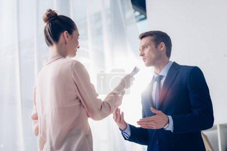 Foto de Vista de ángulo bajo de guapo empresario dando entrevista a periodista con grabadora de voz en office - Imagen libre de derechos