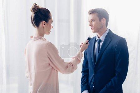 Photo pour Vue latérale du bel homme d'affaires mettant en entrevue au journaliste pour enregistreur de la parole dans le bureau - image libre de droit