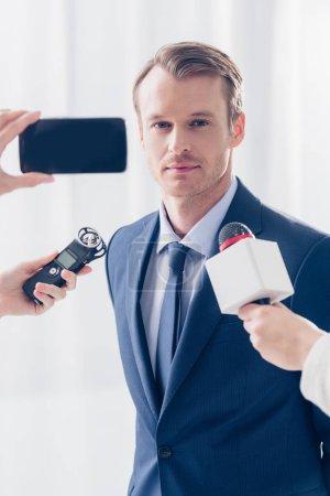 Foto de Apuesto hombre de negocios dando entrevista a los periodistas y mirando a cámara en la oficina - Imagen libre de derechos