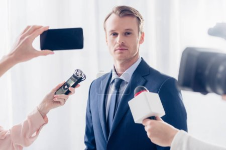 Photo for Handsome businessman giving interview to journalists and looking at camera in office - Royalty Free Image