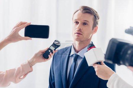 Foto de Hombre de negocios guapo dando entrevista a los periodistas y mirando lejos en oficina - Imagen libre de derechos