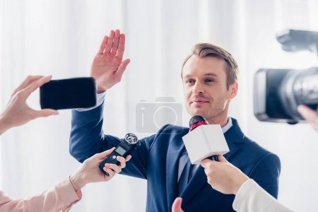 handsome businessman giving interview to journalists in office and waving hand