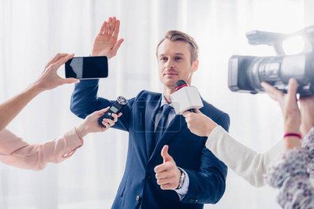Foto de Apuesto hombre de negocios dando entrevista a los periodistas en la oficina, agitando la mano y mostrando el pulgar hacia arriba - Imagen libre de derechos