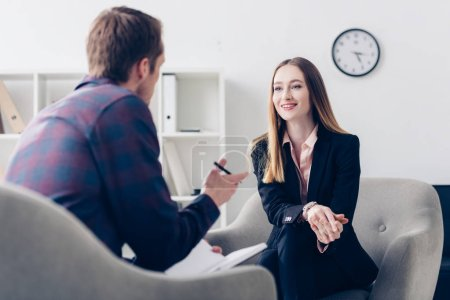 happy businesswoman in suit giving interview to journalist in office