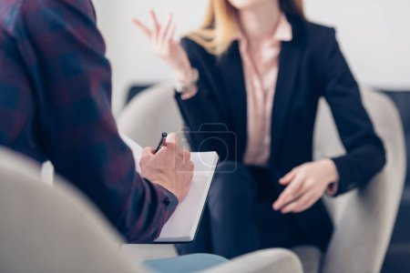 Photo for Cropped image of businesswoman in suit giving interview to journalist and he taking notes in office - Royalty Free Image