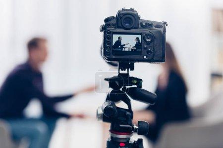 Photo pour Femme d'affaires en costume donnant une interview à un journaliste au bureau, caméra au premier plan - image libre de droit