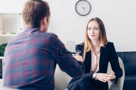 businesswoman in suit giving interview to journalist and looking at him in office