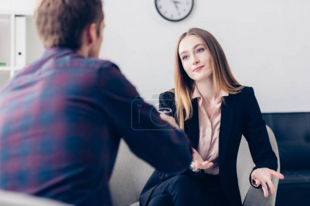 selective focus of businesswoman in suit giving interview to journalist and gesturing in office