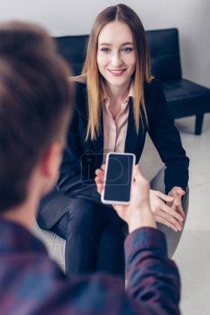 Photo pour Interview journaliste enregistrement femme souriante sur smartphone au bureau - image libre de droit