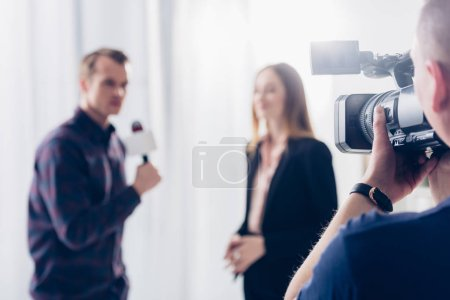 selective focus of businesswoman in suit giving interview to journalist in office, cameraman on foreground