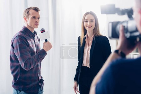 smiling beautiful businesswoman in suit giving interview to journalist and looking at camera in office
