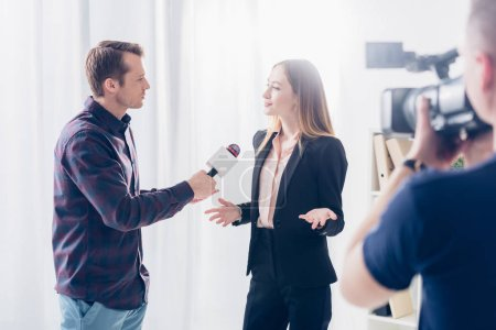 Photo for Beautiful businesswoman in formal wear giving interview to journalist and gesturing in office - Royalty Free Image