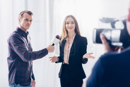 beautiful businesswoman in suit giving interview to journalist and gesturing in office