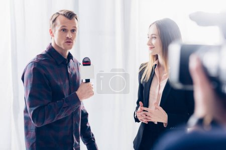 beautiful businesswoman in suit giving interview to surprised journalist in office