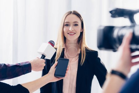 happy beautiful businesswoman in suit giving interview to journalists in office
