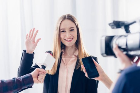 happy attractive businesswoman giving interview to journalists and waving hand in office