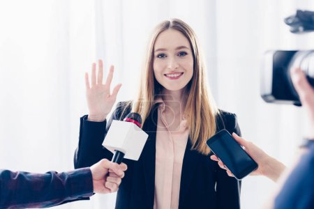 Photo for Smiling attractive businesswoman giving interview to journalists and waving hand in office - Royalty Free Image