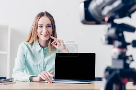 smiling attractive female freelancer recording vlog in office, laptop with blank screen on tabletop