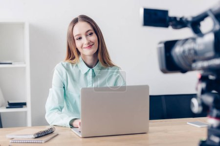 Photo for Cheerful attractive female video blogger recording vlog in office - Royalty Free Image