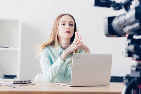 Photo for Serious attractive female video blogger recording vlog in office - Royalty Free Image