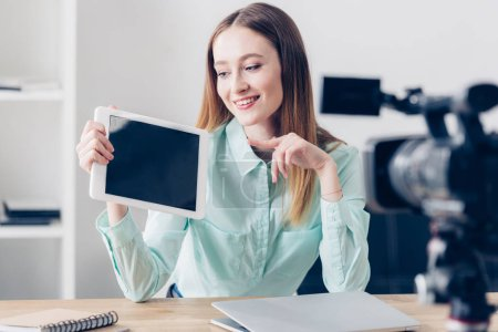 smiling attractive female video blogger recording vlog and pointing on tablet with blank screen in office