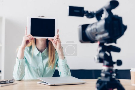 female video blogger recording vlog and covering face with tablet with blank screen in office