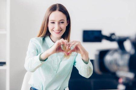 Photo pour Attrayant femme vidéo blogueur heureux vlog d'enregistrement et affichage de coeur avec les doigts au bureau - image libre de droit