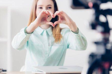 Foto de Enfoque selectivo de atractiva mujer blogger video grabando vlog y mostrando el corazón con los dedos en la oficina - Imagen libre de derechos