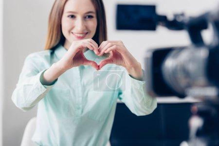 Photo pour Sourire attrayant féminin blogueur vidéo vlog d'enregistrement et affichage de coeur avec les doigts au bureau - image libre de droit