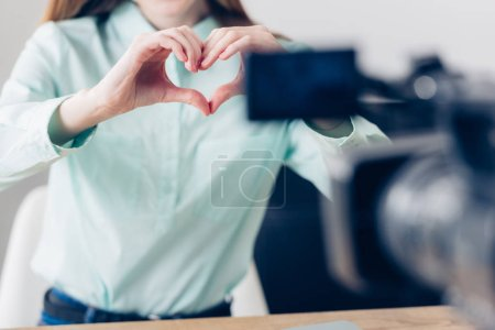 Photo for Cropped image of female video blogger recording vlog and showing heart with fingers in office - Royalty Free Image