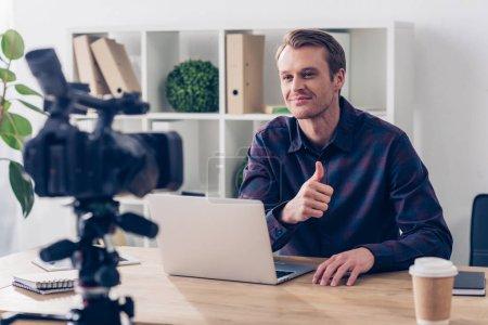 Photo pour Sourire de beau mâle blogueur vidéo enregistrement vlog et apparaître le pouce au bureau - image libre de droit