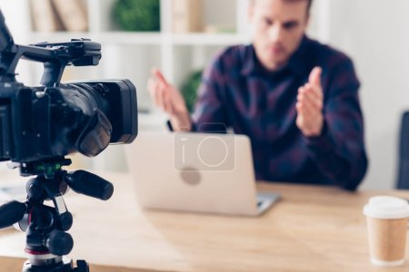 Photo for Selective focus of male video blogger recording video blog and gesturing in office - Royalty Free Image