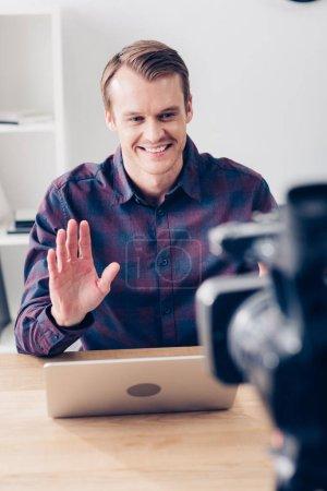 Photo pour Sourire de beau mâle blogueur vidéo enregistrement vlog et en agitant la main au bureau - image libre de droit