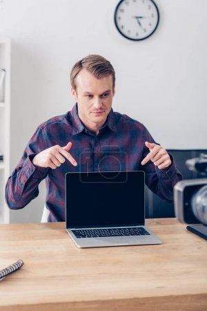 Photo pour Beau mâle blogueur vidéo enregistrement vlog et pointant sur portable avec un écran blanc au bureau - image libre de droit