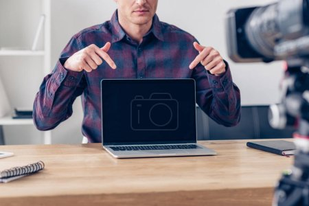 cropped image of male video blogger recording vlog and pointing on laptop with blank screen in office