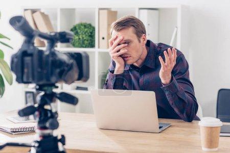 Photo pour Beau mâle blogueur vidéo enregistrement vlog et en regardant les doigts au bureau - image libre de droit