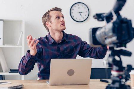 Photo pour Choqué blogueur vidéo mâle beau enregistrement vlog et levant au bureau - image libre de droit
