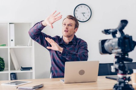 shocked male video blogger recording vlog and covering himself from something in office